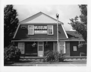 Black and white image of the old Agassiz CPR station with shrubs up front and trees in the background.
